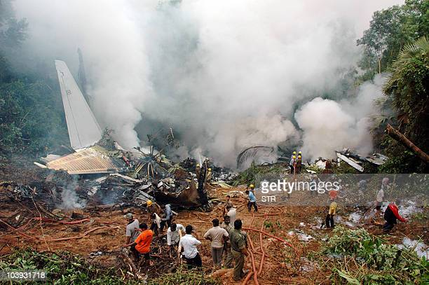 In this file photograph taken on May 22 2010 rescue personnel are seen among the smouldering wreckage of an Air India Boeing 737800 aircraft which...
