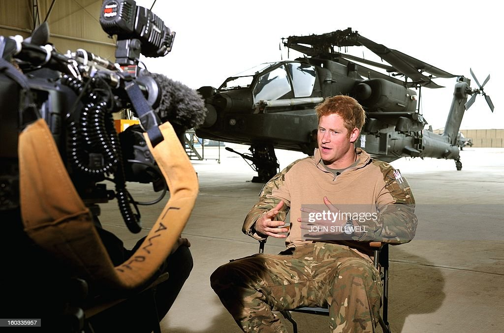 In this file picture taken on December 12, 2012 Britain's Prince Harry (R) is seen giving an interview to a TV crew at Camp Bastion in Afghanistan's Helmand province. Britain's Prince Harry may be home safely from Afghanistan, but he has swapped the crackle of gunfire for the clicking of countless paparazzi cameras. In a series of surprisingly candid interviews before he left Camp Bastion in southern Afghanistan, the third-in-line to the throne spoke not just of his passion for army life, but of the escape it offered from Britain's hungry press. AFP PHOTO/POOL/John STILLWELL