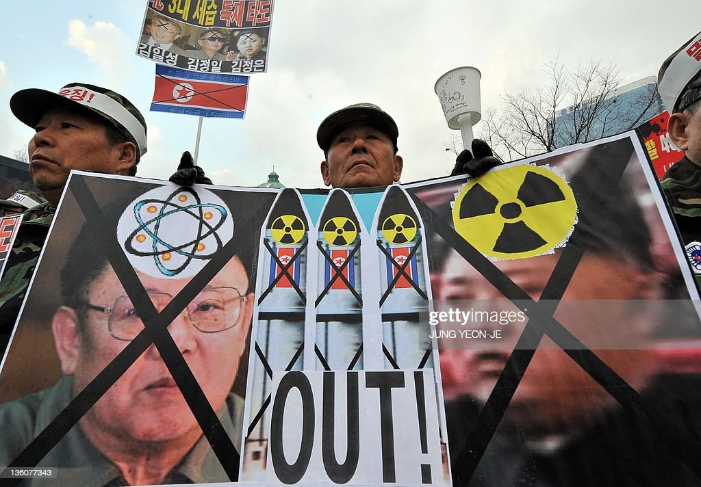 In this file picture taken on December 2 a South Korean veteran holds a placard showing North Korean flags and portraits of Kim JongIl and his son...