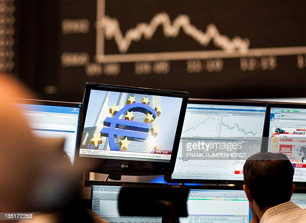 In this file picture taken on November 1 2011 a trader sits in front of screens showing the German DAX index in Frankfurt am Main at the German Stock...