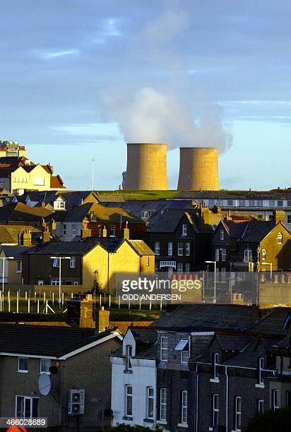 In this file picture taken on September 26 2002 Steam rises from the cooling towers at Sellafield nuclear plant behind the village of Seascale in...