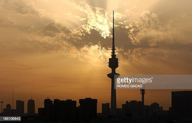 In this file picture the sun sets on March 7 2003 over the Kuwait City skyline marked by the imposing Liberation Tower the national landmark whose...