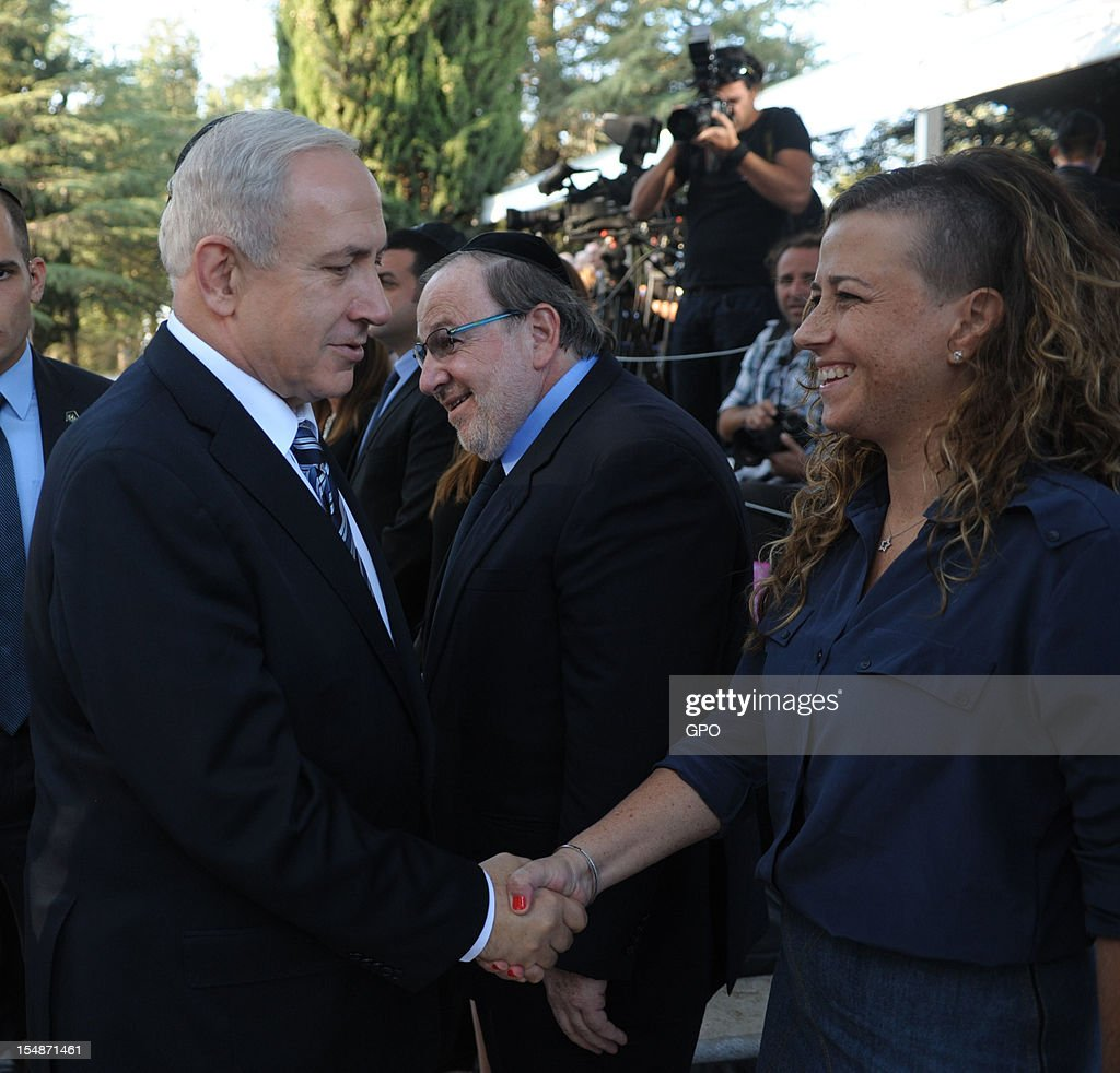 In this GPO handout, Israeli Prime Minister Benjamin Netanyahu shakes hands with Noa Rothman (granddaughter of Yitzhak Rabin) as they stand by the grave of Israeli Prime Minister Yitzhak Rabin during a memorial ceremony marking the 17th anniversary of the assassination of Israeli Prime Minister Yitzhak Rabin, October 28, 2012 in Jerusalem, Israel. Rabin who won the Nobel Peace Prize with Shimon Peres and Yasser Arafat, was assassinated by right-wing Israeli radical Yigal Amir.