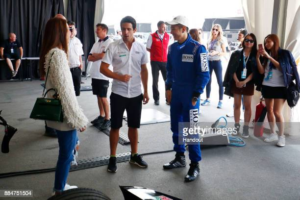 In this handout from FIA Formula E Chinese singer Pakho Chau meets Lucas Di Grassi Audi Sport ABT Schaeffler Audi etron FE04 during the Hong Kong...