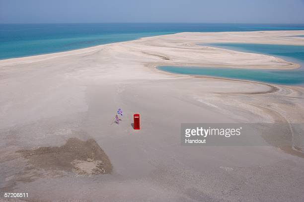 In this handout from Nakheel Co LLC Sir Richard Branson poses next to a phone booth during a photocall on the manmade island known as England in new...