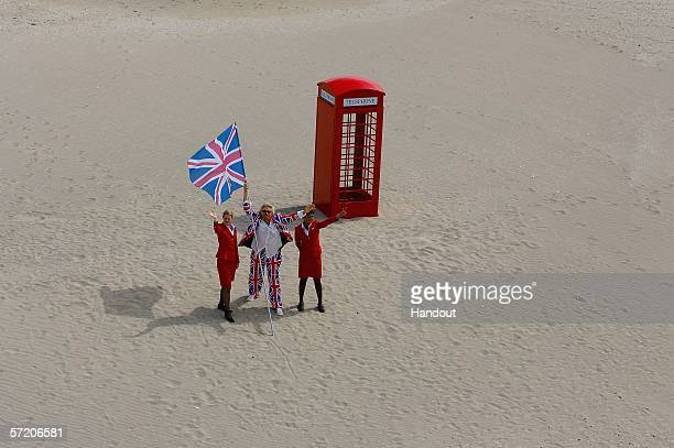In this handout from Nakheel Co LLC Sir Richard Branson poses with Virgins girls next to a phone booth during a photocall on the manmade island known...