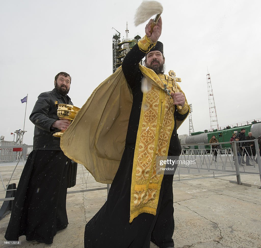 In this handout from NASA, an Orthodox priest blesses members of the media shortly after blessing the Soyuz rocket at the Baikonur Cosmodrome launch pad on March 27, 2013 in Baikonur, Kazakhstan. The launch of the Soyuz rocket is scheduled for March 29 and will send Expedition 35 Soyuz Commander Pavel Vinogradov, and Flight Engineers Chris Cassidy of NASA and Alexander Misurkin of Russia on a five and a half-month mission aboard the International Space Station.