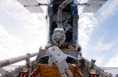 In this handout from NASA Astronauts John Grunsfeld and Andrew Feustel perched on the end of the Space Shuttle Atlantis' remote manipulator system...