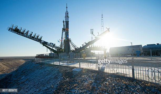 In this handout from NASA The gantry arms begin to close around the Soyuz TMA19M spacecraft after it was raised into a vertical position on the...