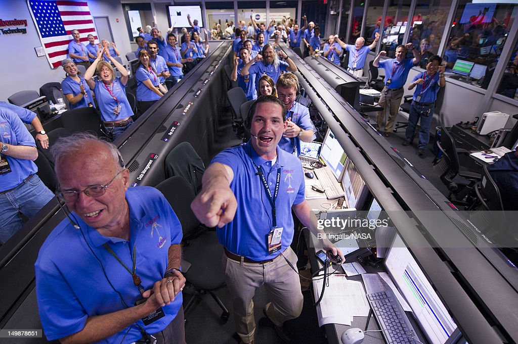 In this handout from NASA, the Mars Science Laboratory (MSL) team in the MSL Mission Support Area reacts after learning the the Curiosity rover has landed safely on Mars and images start coming in at the Jet Propulsion Laboratory, inside the Spaceflight Operations Facility for NASA's Mars Science Laboratory Curiosity rover at Jet Propulsion Laboratory on August 5, 2012 in Pasadena, California. The MSL Rover named Curiosity is equipped with a nuclear-powered lab capable of vaporizing rocks and ingesting soil, measuring habitability, and whether Mars ever had an environment able to support small life forms called microbe.