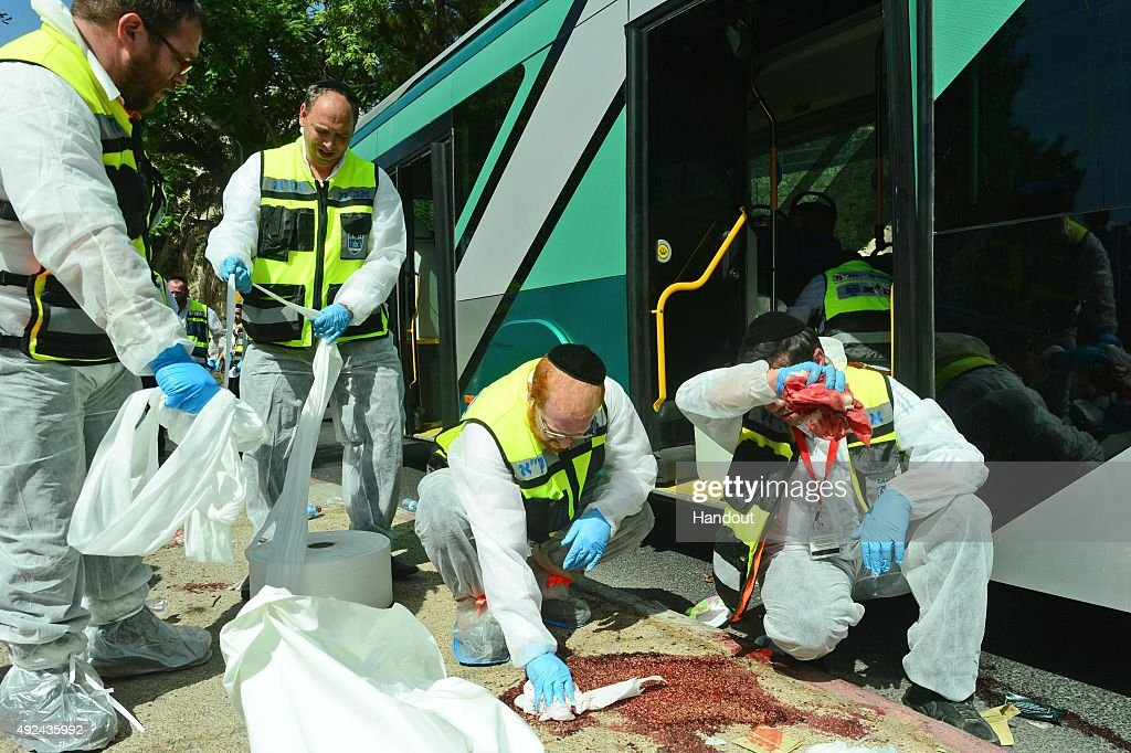 In this handout from the Israeli Government Press Office Ultra Orthodox ZAKA volunteers clean up the scene of a bus attack on October 13 2015 in...