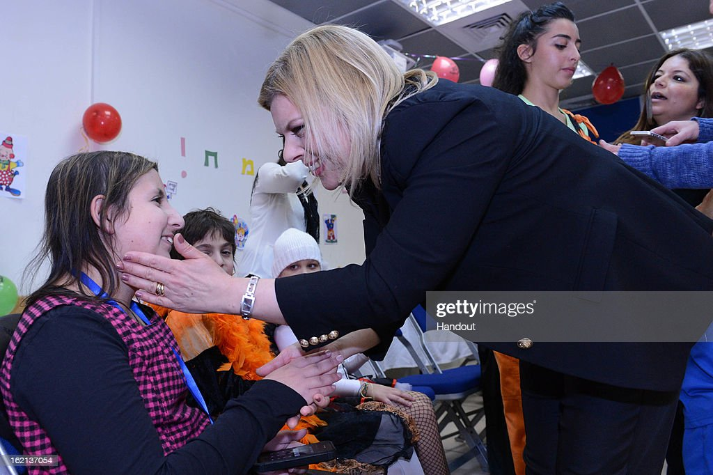 In this handout from the Israeli GPO, Israeli Prime Minister Benjamin Netanyahu's wife Mrs. Sara Netanyahu speaks to a child as she hosts child cancer patients of the 'Rachashei Lev' support center ahead of the Jewish holiday of Purim on February 19, 2013 in an unspecified city in Israel. Netanyahu. Rachashei Lev was founded in 1989 to support children and their families suffering and in treatment from cancer.