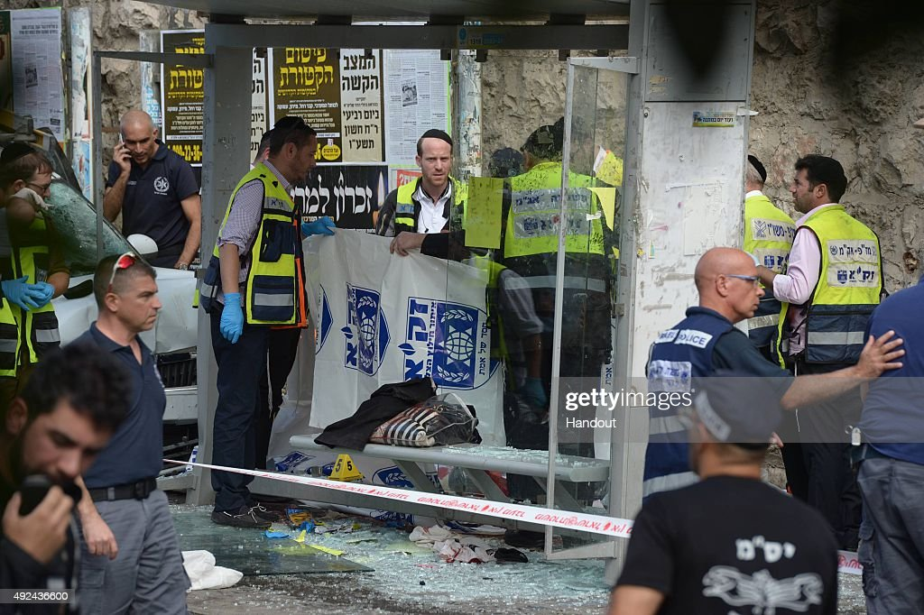 In this handout from the Israeli GPO Ultra Orthodox ZAKA volunteers and security forces attend the scene of an attack at a bus stop in Malchei...
