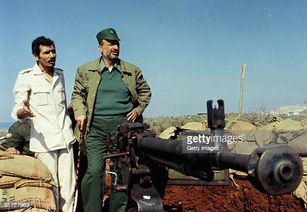 In this handout from the Palestinian Press Office PLO Chairman Yasser Arafat stands next to a machinegun in 1983 in an unspecified location in...