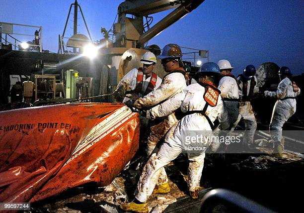 In this handout from the US Department of Defense crewmembers from USCGC Harry Claiborne remove an oil covered boom from the ocean May 8 2010 in the...