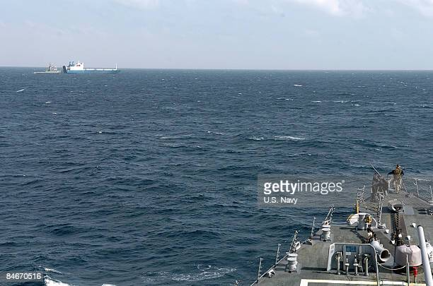 In this handout from the US Navy A watch stander on the bow of USS Mahan monitors the fleet ocean tug USNS Catawba as it makes preparations to...
