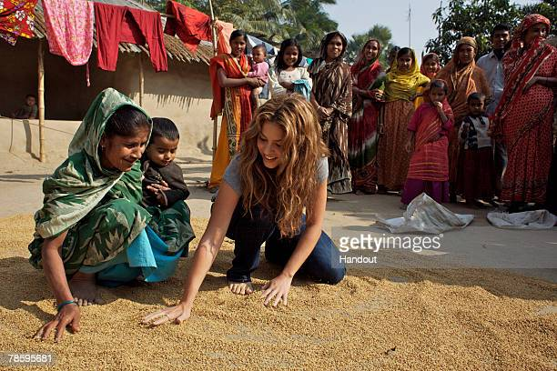In this handout from United Nations Children's Fund Shakira an UNICEF ambassador sits with a woman in front of her house to learn how women process...