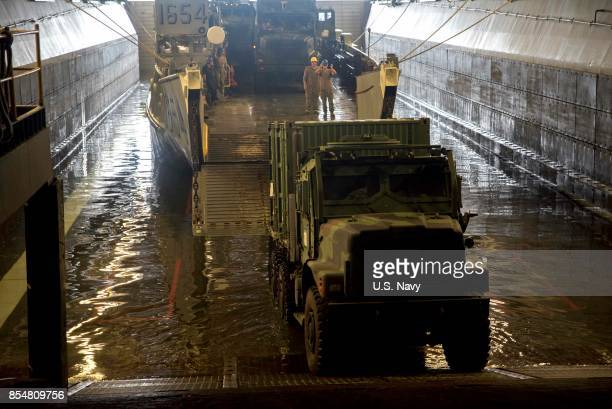 In this handout imade provided by the USNavy Vehicles carrying generators and other equipment embark a landing craft utility in the well deck of the...