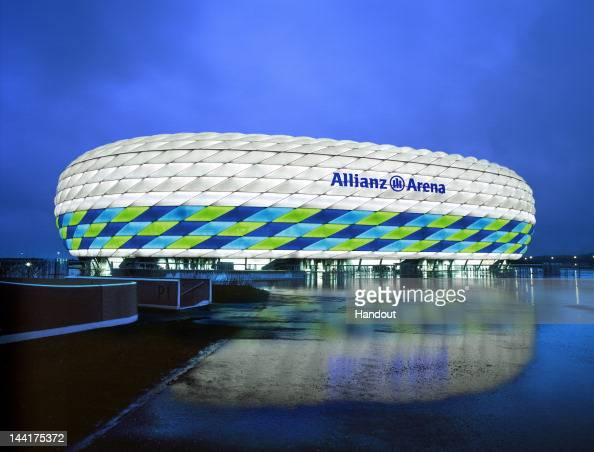 In this handout image from the Allianz Group the Allianz Arena is illuminated with white green and blue lights ahead of the UEFA Champions League...
