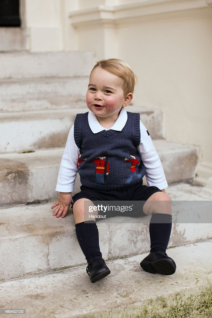 In this handout image of three released on December 13, 2014 by Kensington Palace, Prince George sits for his official Christmas picture in a courtyard at Kensington Palace in late November of 2014 in London, England.