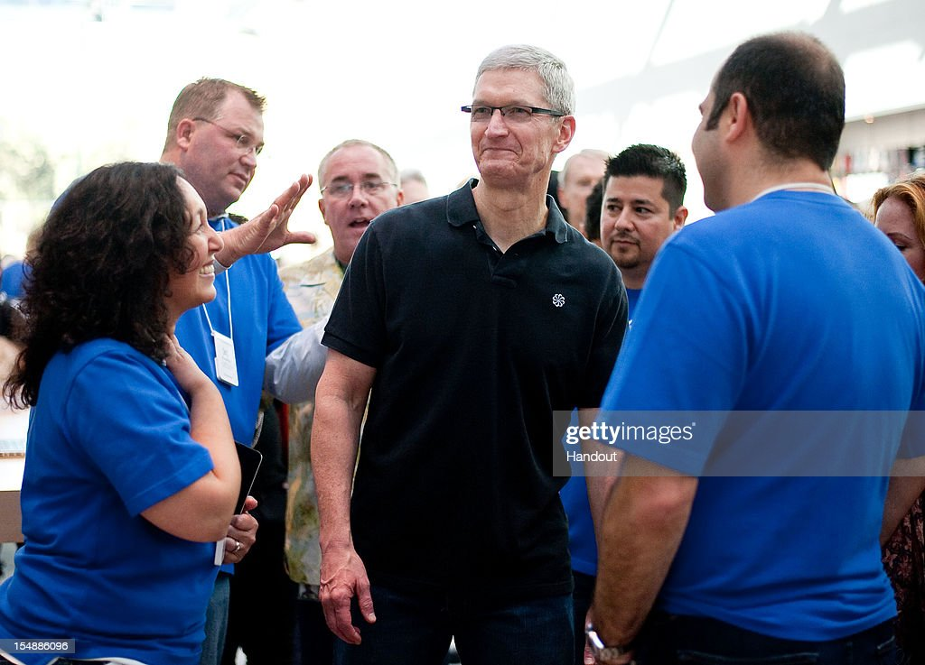 In this handout image provided by Apple, Apple store employees greet CEO Tim Cook at the new Apple Store on October 27, 2012 in Palo Alto, California.
