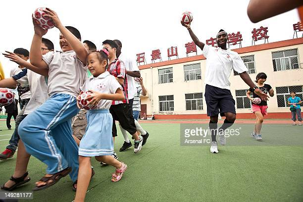 In this handout image provided by Arsenal FC Johan Djourou plays football with children as he visits the Miaopu Huanghuang School which is funded by...