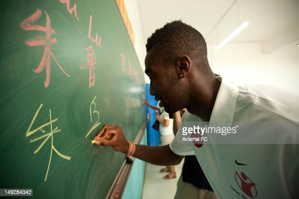 In this handout image provided by Arsenal FC Johan Djourou writes on a blackboard as he visits the Miaopu Huanghuang School which is funded by Save...