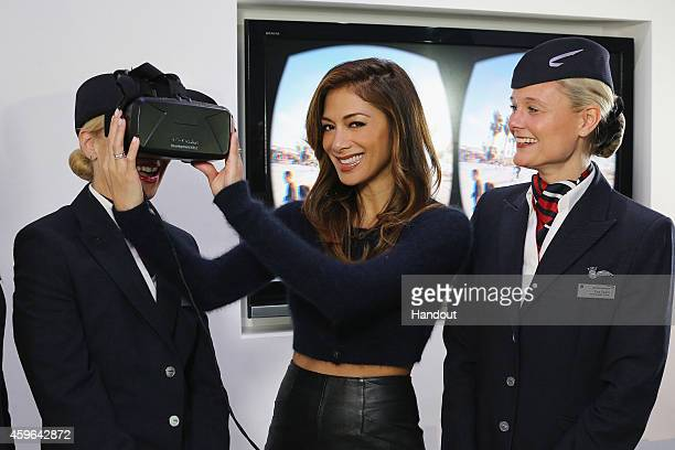 In this handout image provided by British Airways Nicole Scherzinger tries on an Oculus Rift headset that British Airways will use as a virtual...