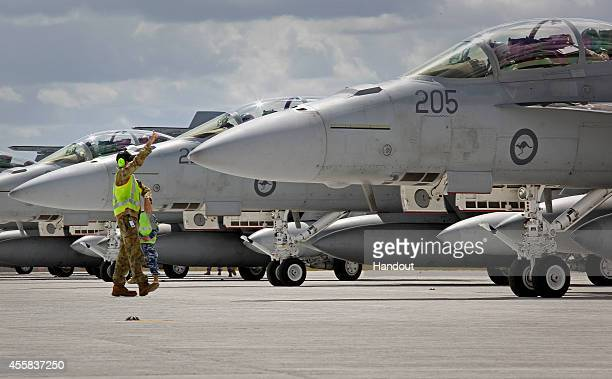 In this handout image provided by Commonwealth of Australia ground crew assist as RAAF F/A18F Super Hornets prepare for departure to the Middle East...