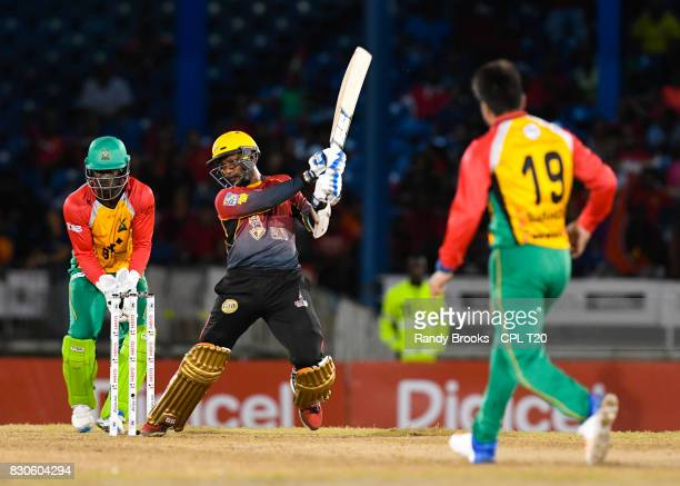 In this handout image provided by CPL T20 Denesh Ramdin of Trinbago Knight Riders hits 4 as Chadwick Walton and Rashid Khan of Guyana Amazon Warriors...