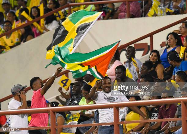 In this handout image provided by CPL T20 Fans of Guyana Amazon Warriors and Jamaica Tallawahs wave flags during Match 15 of the 2017 Hero Caribbean...