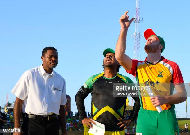 In this handout image provided by CPL T20 Martin Guptill of Guyana Amazon Warriors toss the coin as Kumar Sangakkara of Jamaica Tallawahs and match...