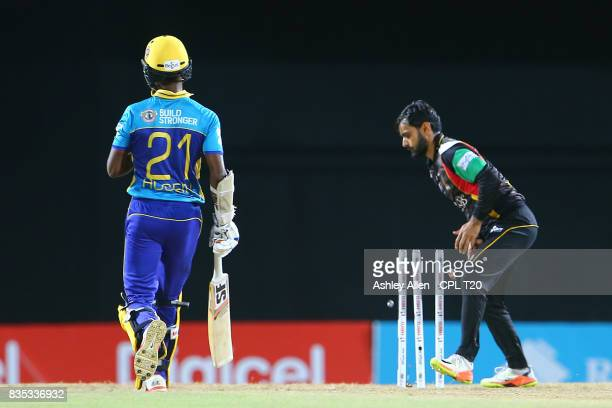 In this handout image provided by CPL T20 Mohammed Hafeez of St Kitts and Nevis Patriots takes the bails off to run out Akeal Hosein of the Barbados...