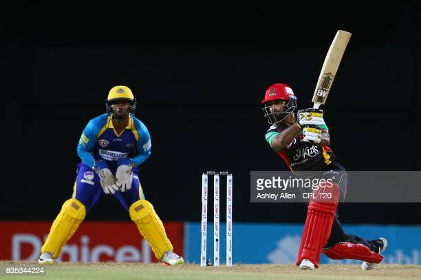 In this handout image provided by CPL T20 Mohammed Hafeez of St Kitts and Nevis Patriots hits four through the offside as Nicholas Pooran of the...