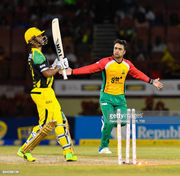 In this handout image provided by CPL T20 Rashid Khan of Guyana Amazon Warriors celebrate the dismissal of Lendl Simmons of Jamaica Tallawahs during...
