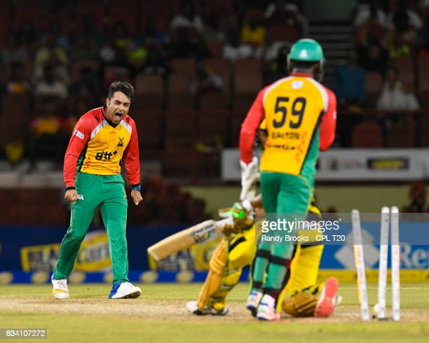 In this handout image provided by CPL T20 Rashid Khan of Guyana Amazon Warriors celebrates the dismissal of Jonathan Foo of Jamaica Tallawahs during...