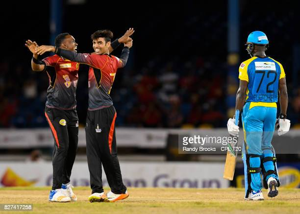 In this handout image provided by CPL T20 Shadab Khan and Dwayne Bravo of Trinbago Knight Riders celebrates the dismissal of Andre Fletcher of St...