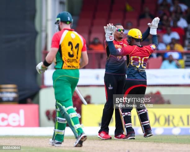 In this handout image provided by CPL T20 Sunil Narine and Denesh Ramdin of Trinbago Knight Riders celebrate the dismissal of Martin Guptill of...