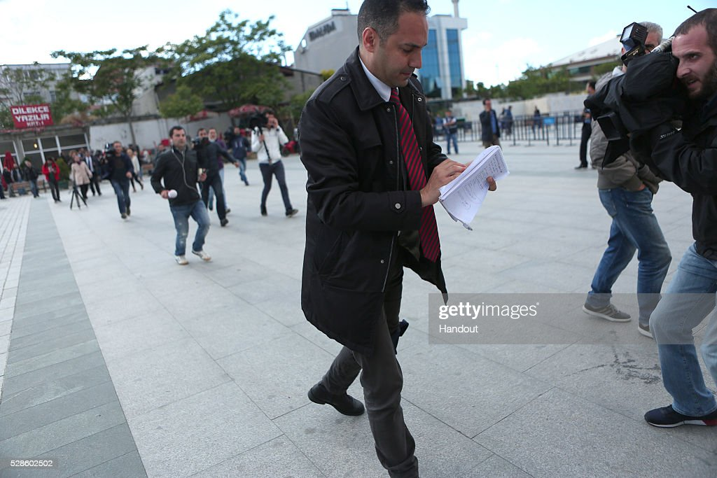In this handout image provided by Cumhuriyet Newspaper, A reporter covering his trial appeared to have been injured walks away during the attack by an assailant, 40-year-old Murat Sahin who attempted to shoot prominent Turkish journalist Can Dundar is caught outside a courthouse in Istanbul May 6, 2016, Turkey. Dundar, the editor-in-chief of the opposition Cumhuriyet newspaper, was unharmed but a reporter covering his trial appeared to have been injured. Dundar and Erdem Gul, the newspaper's Ankara bureau chief, could face life in jail on espionage charges and attempting to topple the government for publishing footage that purported to show Turkey's state intelligence agency ferrying weapons into Syria in 2014.