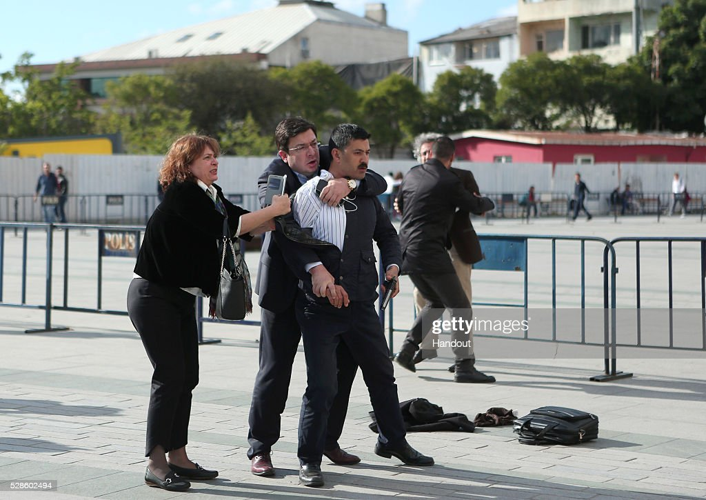 In this handout image provided by Cumhuriyet Newspaper, Assailant, 40-year-old Murat Sahin who attempted to shoot prominent Turkish journalist Can Dundar is held by Dilek Dundar, wife of Can Dundar, and an unidentified man. Can Dundar is seen in the background being protected by TV reporter yagiz senkal who was injured during the attack outside a courthouse in Istanbul May 6, 2016, Turkey. Dundar, the editor-in-chief of the opposition Cumhuriyet newspaper, was unharmed but a reporter covering his trial appeared to have been injured. Dundar and Erdem Gul, the newspaper's Ankara bureau chief, could face life in jail on espionage charges and attempting to topple the government for publishing footage that purported to show Turkey's state intelligence agency ferrying weapons into Syria in 2014.