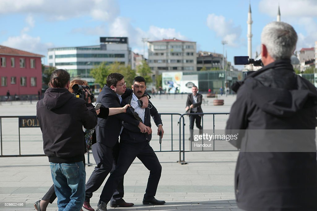 In this handout image provided by Cumhuriyet Newspaper, Assailant, 40-year-old Murat Sahin who attempted to shoot prominent Turkish journalist Can Dundar is caught by Dilek Dundar, wife of Can Dundar, and an unidentified man outside a courthouse in Istanbul May 6, 2016, Turkey. Dundar, the editor-in-chief of the opposition Cumhuriyet newspaper, was unharmed but a reporter covering his trial appeared to have been injured. Dundar and Erdem Gul, the newspaper's Ankara bureau chief, could face life in jail on espionage charges and attempting to topple the government for publishing footage that purported to show Turkey's state intelligence agency ferrying weapons into Syria in 2014.