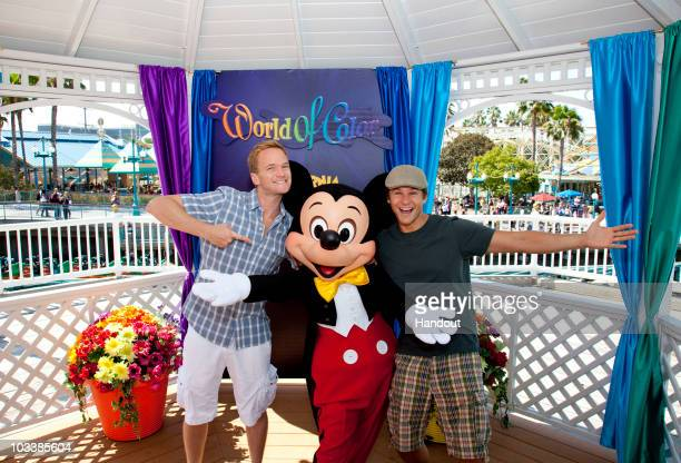 In this handout image provided by Disney Neil Patrick Harris and David Burtka pose with Mickey Mouse at Paradise Pier site of the hit nighttime...
