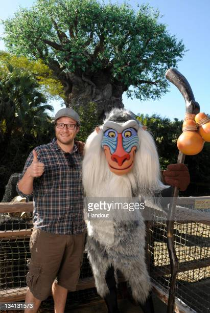 In this handout image provided by Disney Parks actor comedian and animated film voice actor Seth Rogen poses with Disney's character Rafiki from 'The...
