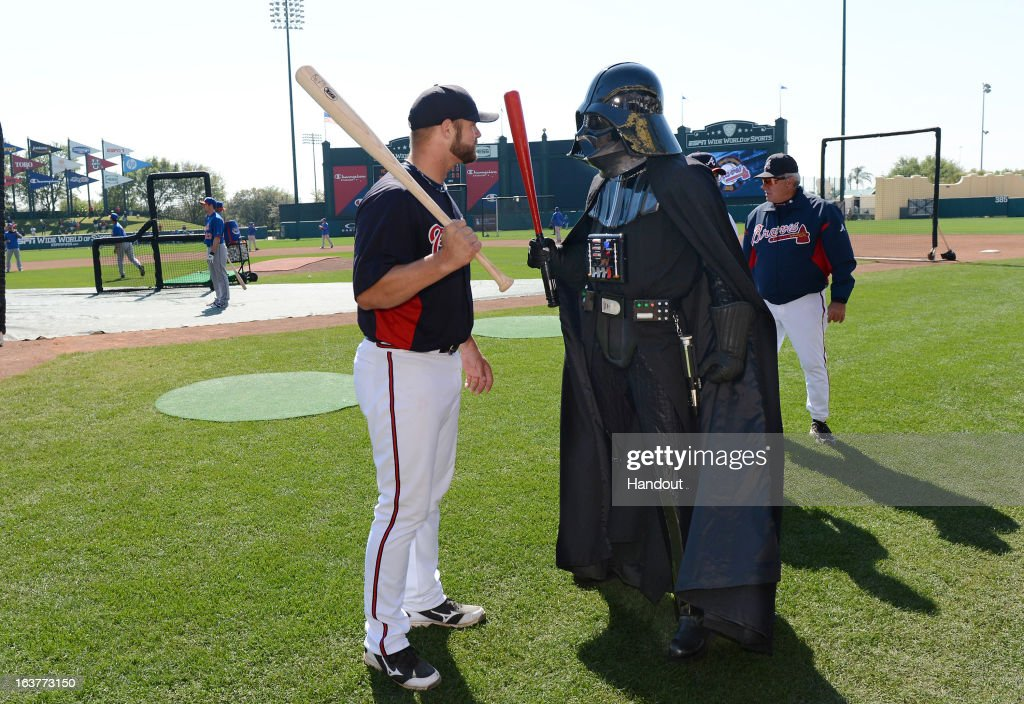 In this handout image provided by Disney Parks, Atlanta Braves catcher Evan Gattis meets Darth Vader before a Braves spring training game at Champion Stadium at ESPN Wide World of Sports Complex March 15, 2013 in Lake Buena Vista, Florida. Friday's Braves and Mets MLB game was 'Star Wars Day' at the Walt Disney World ballpark.