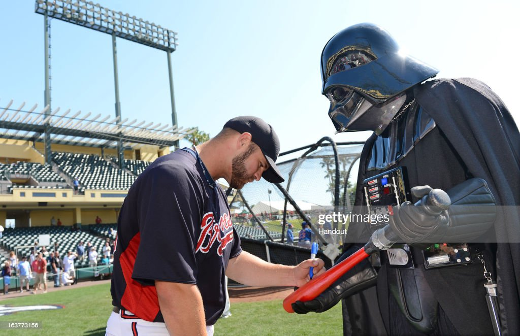 In this handout image provided by Disney Parks, Atlanta Braves catcher Evan Gattis autographs a lightsaber bat for Darth Vader before a Braves spring training game at Champion Stadium at ESPN Wide World of Sports Complex March 15, 2013 in Lake Buena Vista, Florida. Friday's Braves and Mets MLB game was 'Star Wars Day' at the Walt Disney World ballpark.