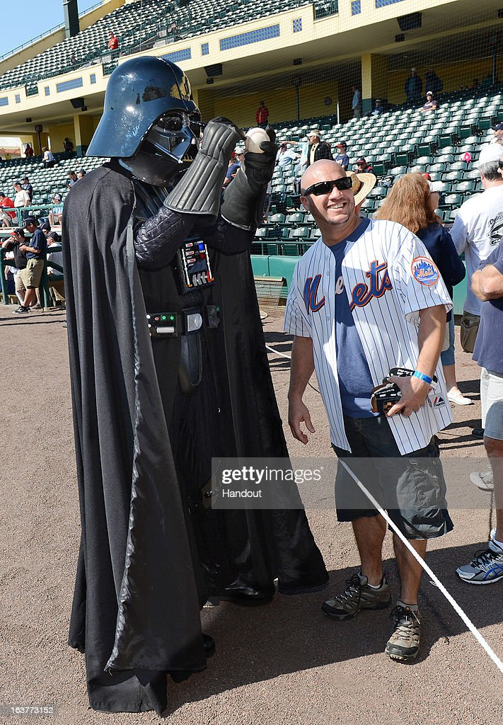 In this handout image provided by Disney Parks Darth Vader autographs a baseball for Richard Ward of Orlando Florida before a Braves spring training...