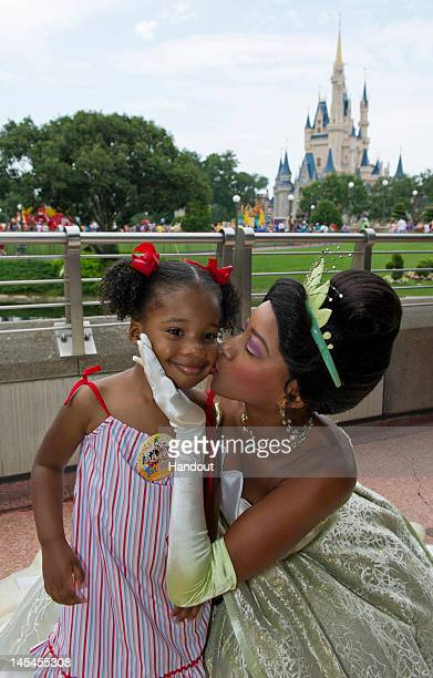 In this handout image provided by Disney Parks Disney's Princess Tiana gives a kiss to Yolanda King granddaughter of the late civil rights leader Dr...
