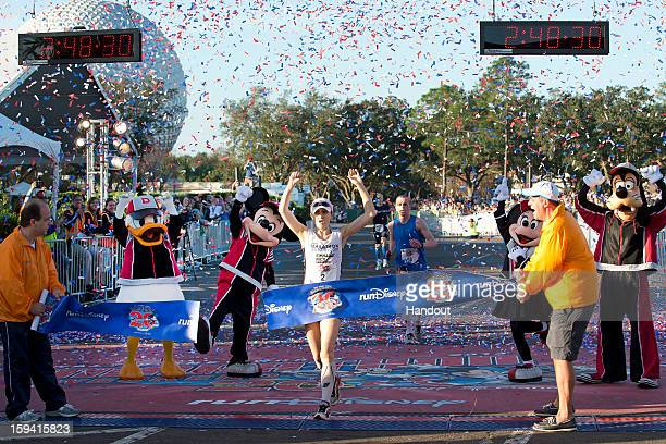 In this handout image provided by Disney Parks Renee High of Virginia Beach Va crosses the finish line to claim her second consecutive Walt Disney...