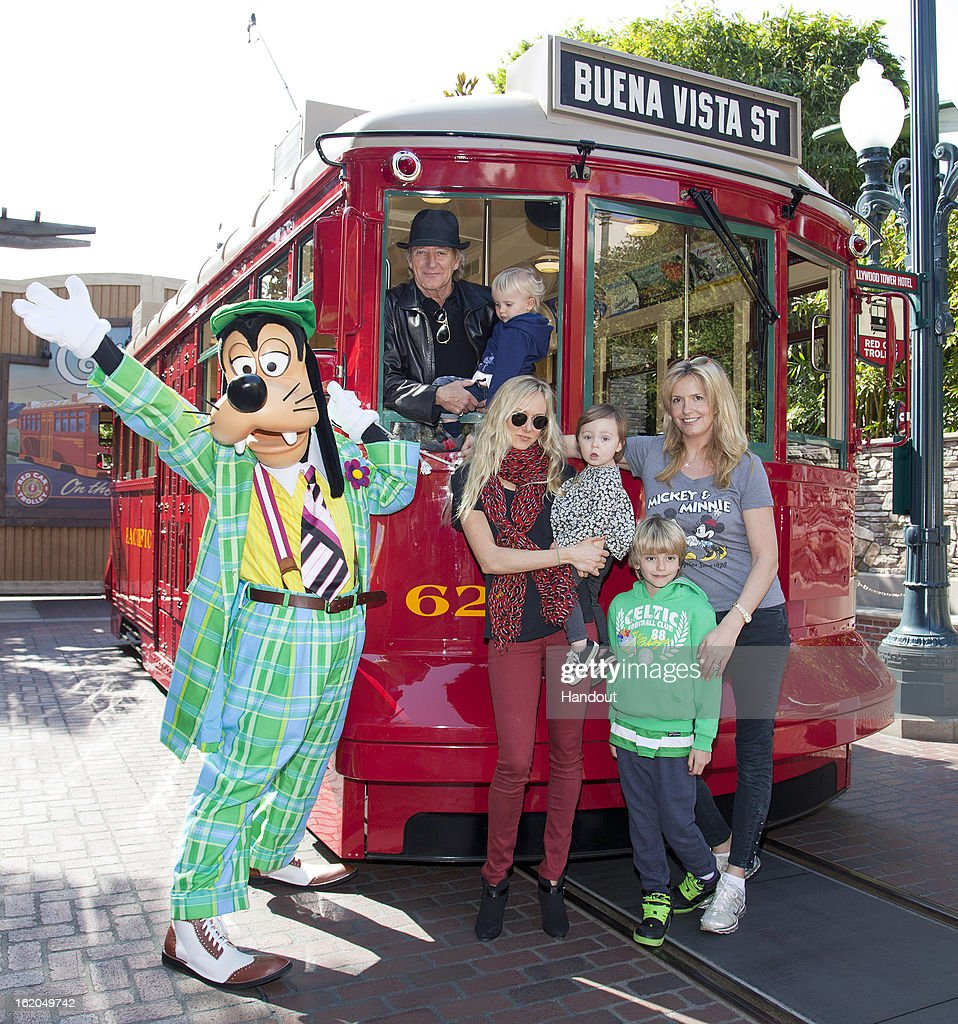 In this handout image provided by Disney Parks, Rod Stewart, his wife Penny (R), and their sons, Aiden, 2, and Alastair 7, celebrate Aiden's second birthday along with Stewart's daughter Kimberley (C) and her daughter Delilah, 1, with Goofy on the Red Car Trolley at Disney California Adventure park February 18, 2013 in Anaheim, California.