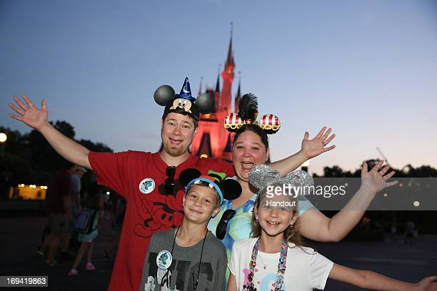 In this handout image provided by Disney Parks the Moore family from Seminary Miss Nick Adrian Stacie and Hannah pose in front of Cinderella Castle...
